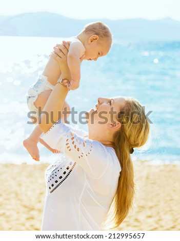 Happy family. Young mother throws up baby in the sky isolated outside sea, mountains background on sunny day. Portrait mother and little son on the beach. Positive human emotions, feelings, emotions.