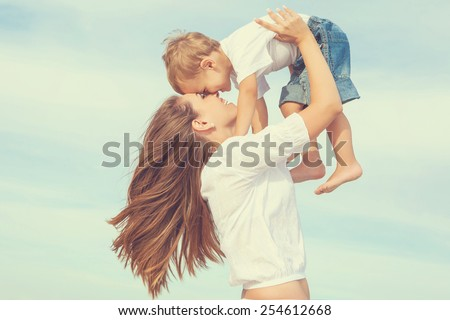 Happy family. Young mother throws up baby in the sky, on sunny day. Portrait mom and little son on the beach. Positive human emotions, feelings, joy. - stock photo