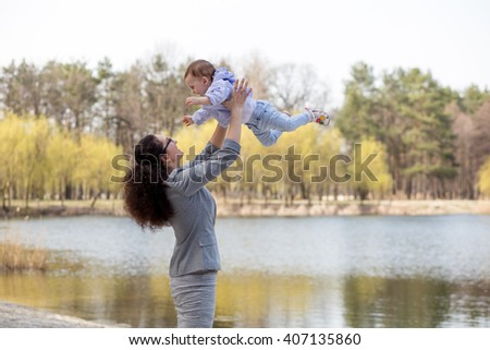 Happy family. Young mother throws up baby in the sky, on sunny day. Portrait mother and little daughter. Positive human emotions, feelings. - stock photo