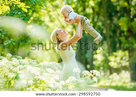 Happy family. Young mother throws up baby in the sky, on sunny day. Portrait mother and little son in the park. Positive human emotions, feelings, emotions. - stock photo