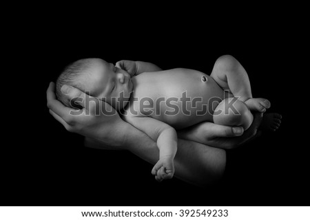 happy family , young parents holding a newborn baby in her arms , who is asleep and gently hugged him, black and white photo on a black background , a lot of affection and love .