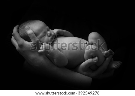 happy family , young parents holding a newborn baby in her arms , who is asleep and gently hugged him, black and white photo on a black background , a lot of affection and love . - stock photo