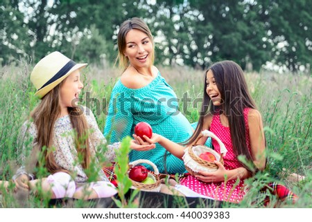 happy family young pregnant woman and children daughters on picnic