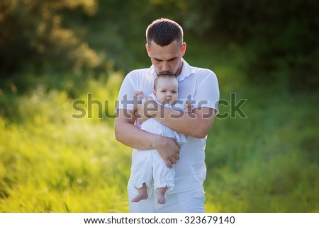 Happy family: young strong healthy father in white clothes walking with his new-born daughter in the park on a sunny summer day.  - stock photo