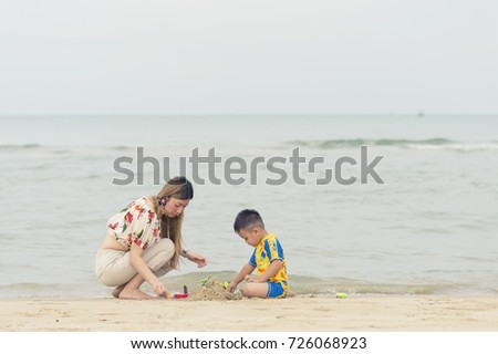 Happy family.Young woman playing with her son on the beach during holiday on sea background.