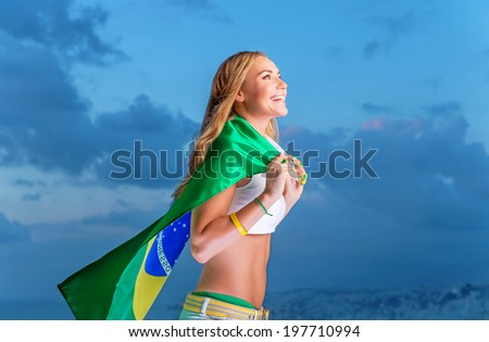 Happy fan of Brazilian football team, cheerful pretty girl on stadium cheering in support, holding up big national flag of Brazil, active people traveling to watch football games - stock photo