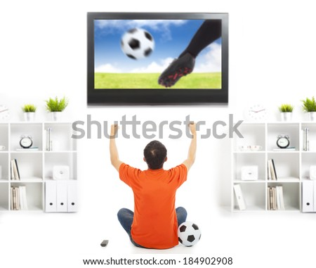 happy fan watching soccer game and raised hands - stock photo