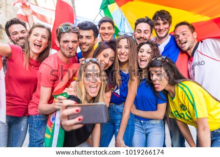 Happy fans supporters taking a selfie all together. Fans from Italy, Germany, Spain, Brazil and other countries enjoying time after a match. Sport, respect and fair play concepts