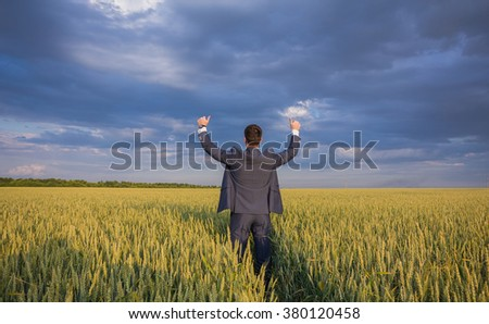 happy farmer, businessman, standing in wheat field over wind turbines background with his hands up and thumbs up - stock photo