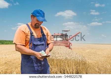 happy farmer during harvest wheat - stock photo