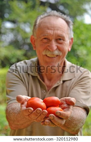 Happy farmer holding tomatoes from crop.