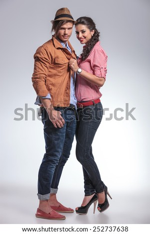 Happy fashion couple posing together on studio background. She is pulling his jacket. - stock photo