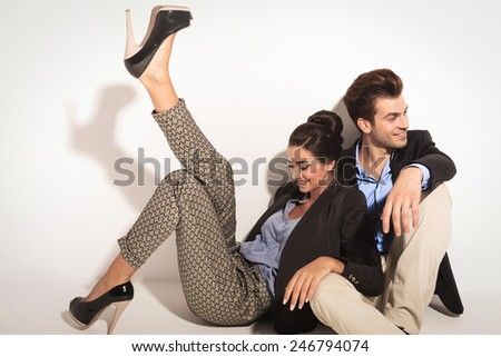Happy fashion couple sitting together on the floor laughing while looking away from the camera. The woman is leaning on her lover while holding one leg up. - stock photo