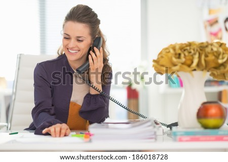 Happy fashion designer talking phone in office - stock photo