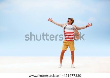 happy fashion man walking around beach. blue sky background. - stock photo