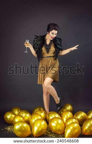 Happy fashion woman dancing drinking champagne, dressed in a gold dress and feathers collar, surrounded with yellow balloons . New Year's Eve Party - stock photo