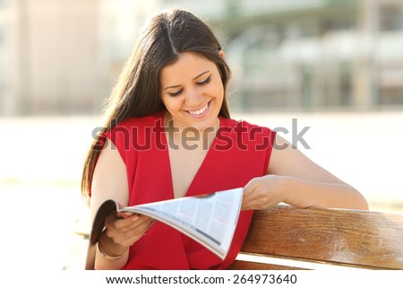 Happy fashion woman reading a magazine in an urban park wearing a red blouse - stock photo
