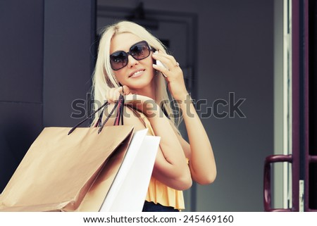 Happy fashion woman with shopping bags calling on mobile phone - stock photo