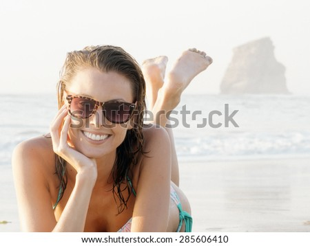 happy fashion young woman smiling in bikini and sunglasses lying on beach, with wet hair