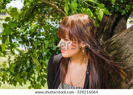 Happy fashionable brunette looking away a lot of copy space on tree leaves - stock photo