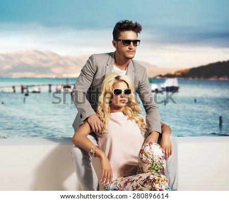 Happy fashionable couple on sunny vacation day - stock photo