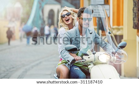 Happy fashionable couple riding on scooter - stock photo