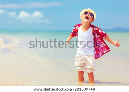 happy fashionable kid boy enjoys life on summer beach - stock photo
