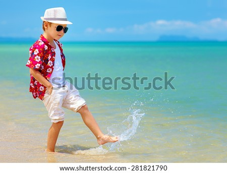 happy fashionable kid boy walking in surf on tropical beach - stock photo