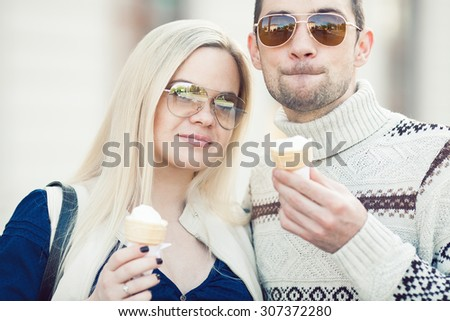 Happy fashionable pregnant couple eating ice cream in trendy casual clothing and eyeglasses. Modern urban, street style. Close up. Outdoor shot
