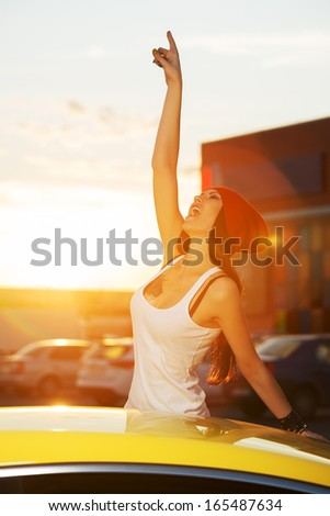 Happy fashionable woman standing at the car - stock photo