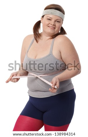 Happy fat woman measuring waistline by tape measure, smiling. - stock photo