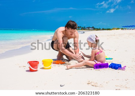 Happy father and adorable little daughter playing with beach toys - stock photo