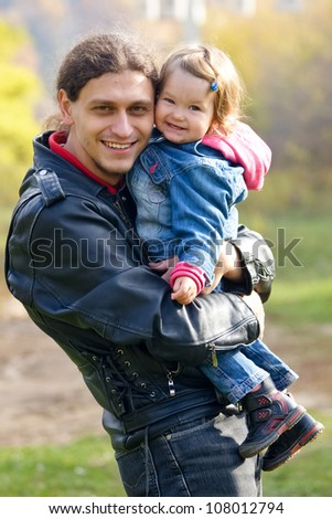 Happy father and baby daughter smiling and hugging for a walk in the park. Man wearing a black leather jacket, a girl in a denim suit. Paternal and child love. Summer holiday.