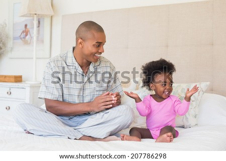 Happy father and baby girl sitting on bed together at home in the bedroom - stock photo