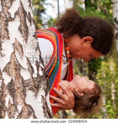 Happy father and baby playing and laughing in birch forest. Baby sitting in a sling. - stock photo