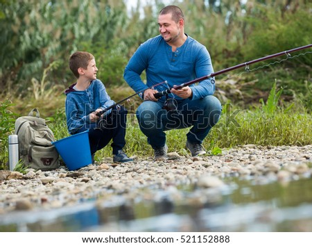 Happy father and boy fishing with rods in summer day