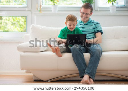 Happy father and child playing with laptop at home - stock photo