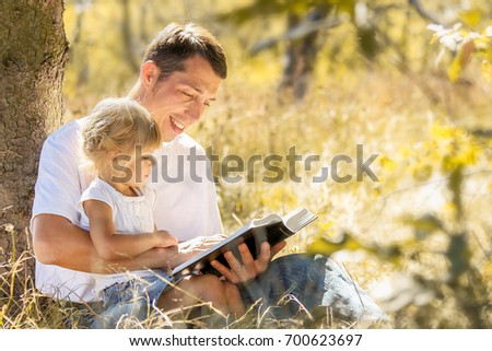 Happy father and child reading a book in nature