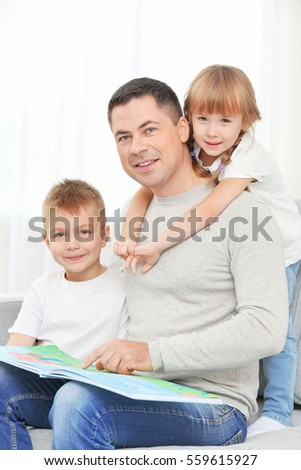Happy father and children reading book on couch