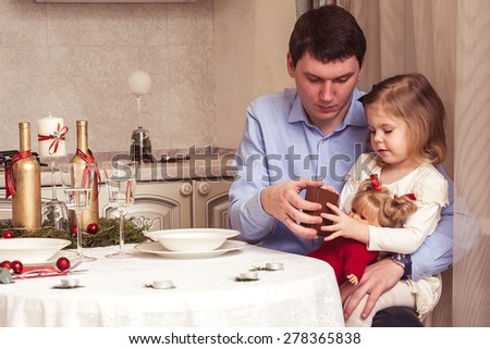Happy father and cute little daughter at the festive holiday table - stock photo