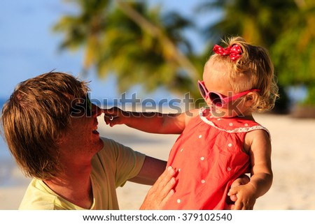 Happy father and cute little daughter play at beach - stock photo
