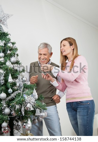 Happy father and daughter decorating Christmas tree together at home - stock photo