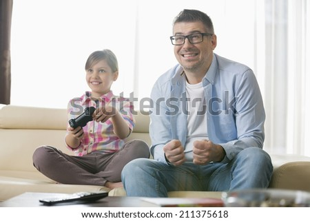 Happy father and daughter enjoying video game in living room - stock photo