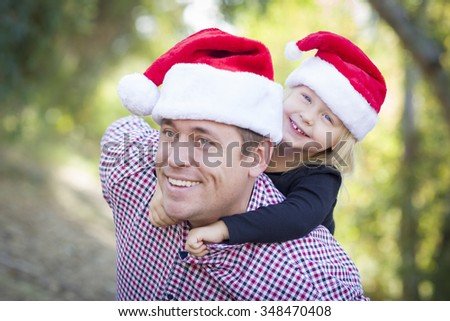 Happy Father and Daughter Having Fun Wearing Santa Hats Outdoors. - stock photo