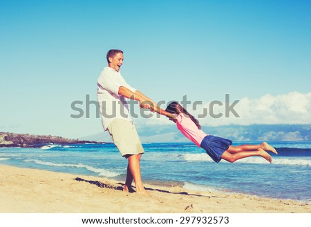 Happy father and daughter playing together at the beach. Fun vacation summer lifestyle.
