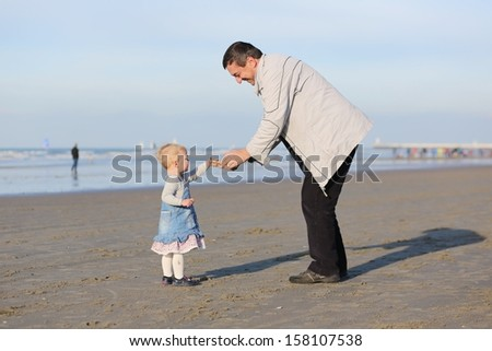 Happy father and daughter playing together on the beach on a sunny autumn day
