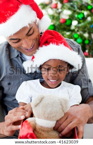 Happy father and daughter playing with Christmas gifts at home - stock photo