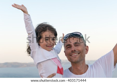 Happy father and daughter relaxing on a beautiful beach.