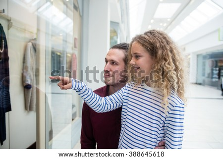 Happy father and daughter standing in front of shop window and looking at apparels - stock photo