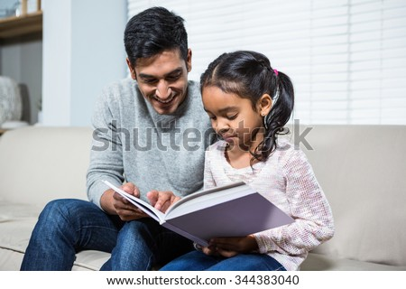 Happy father and daughter using laptop on the sofa in living room - stock photo